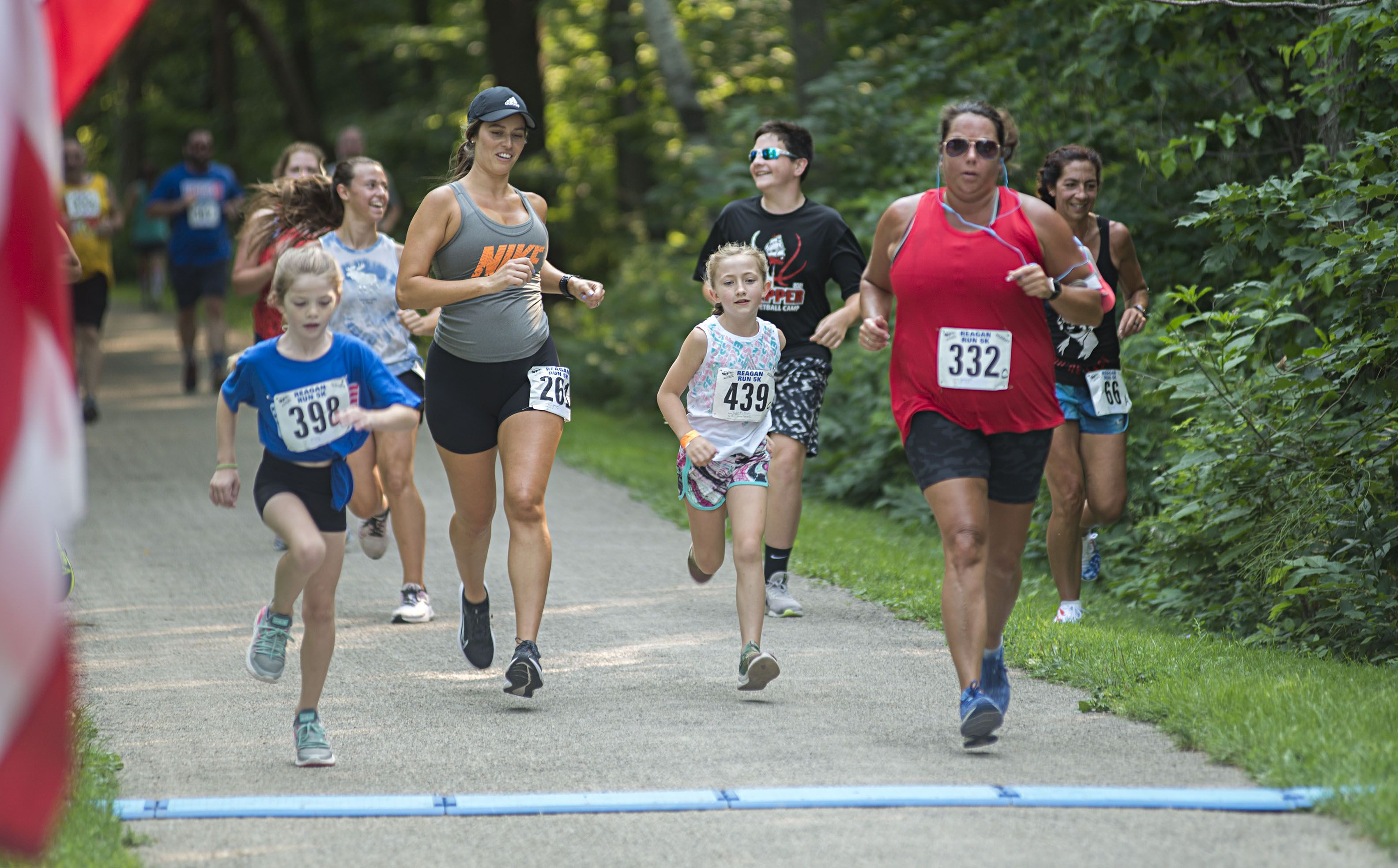 A group of runners come in to finish their race Saturday during the Reagan Run. This year's course started at Lowell Park and finished at the Washington Avenue bike path. Organizers hope to have the original course back up and running next year.