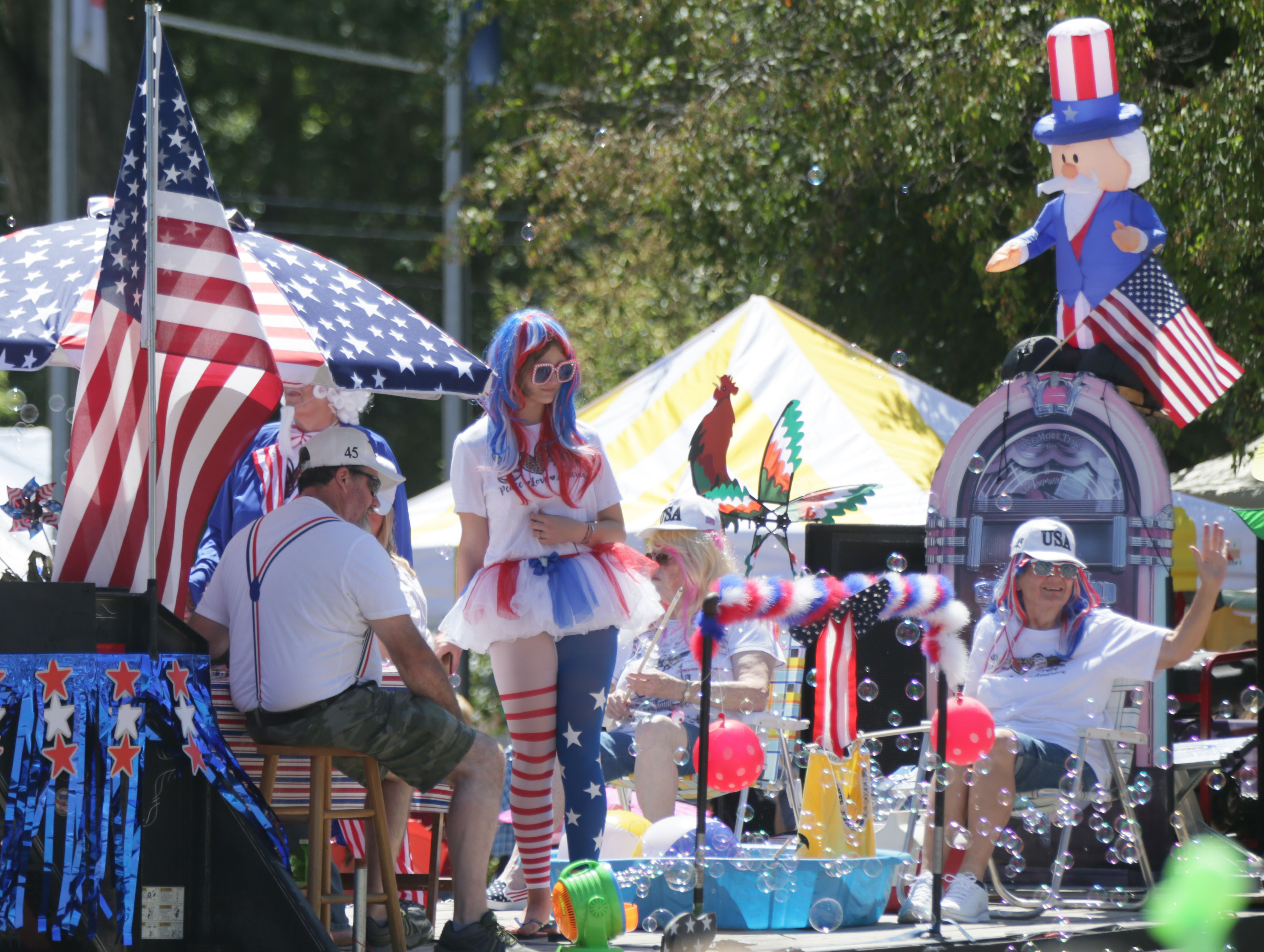 GES Production Sound Services in Princeton ride in the patriotic float in the 74th annual Sweet Corn Festival in Mendota on Sunday Aug. 15, 2021.