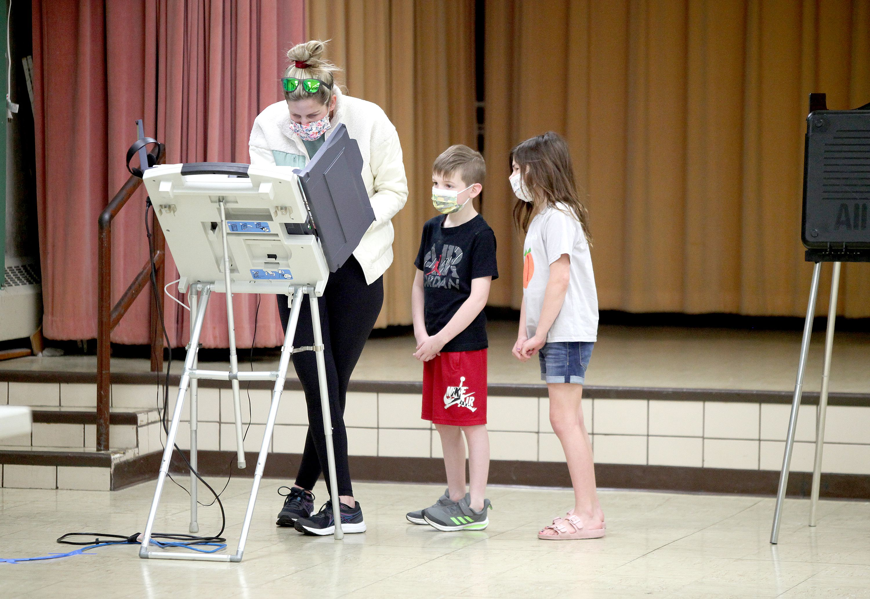 Downers Grove resident Ilana Roth votes as her children, Trey, 8, and Reese, 10, look on at the Downers Grove Village Hall on Tuesday, April 6, 2021.