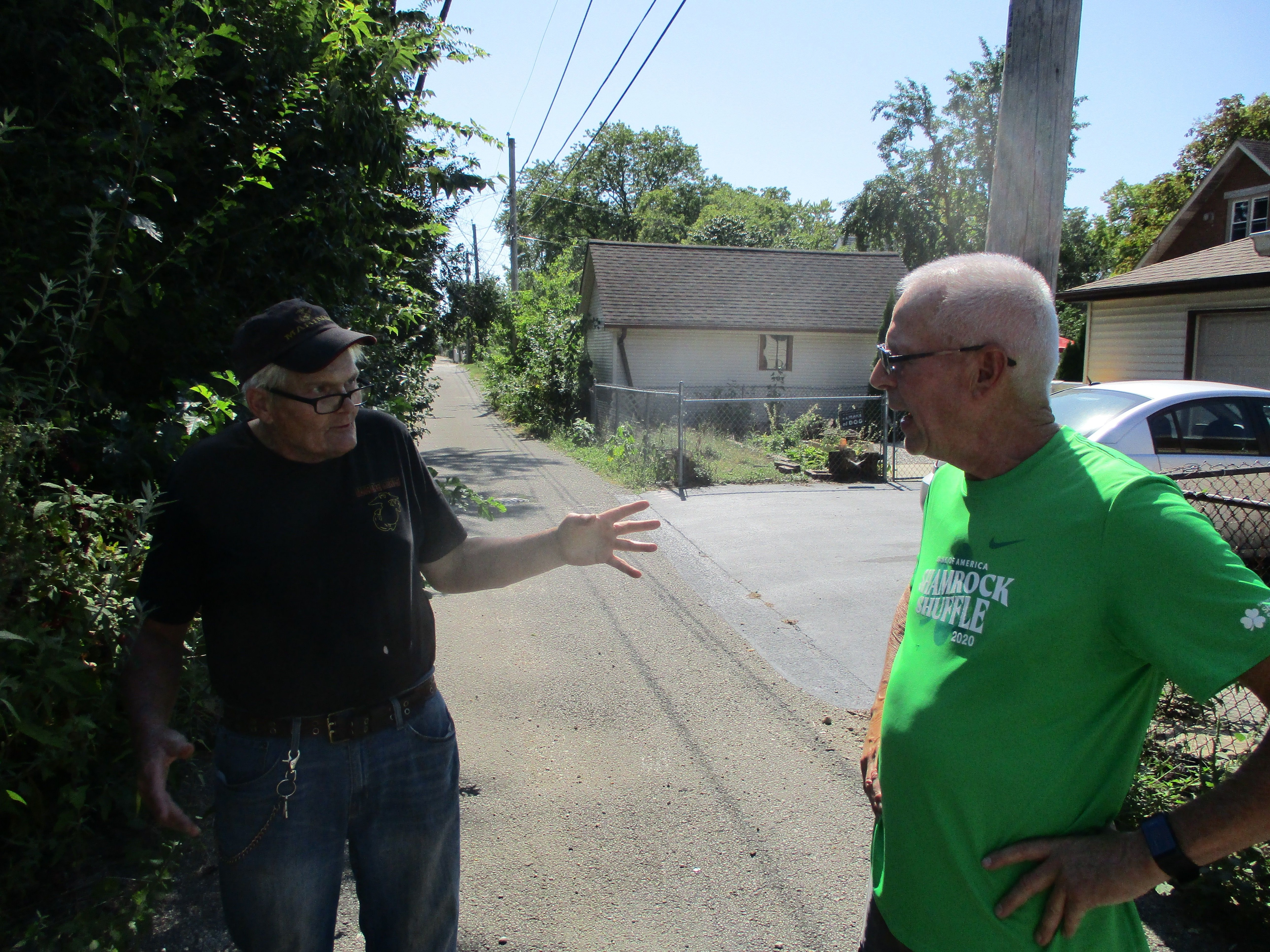 John Sheridan (right) talks with neighbor Gene Sorensen in the alley behind their houses.