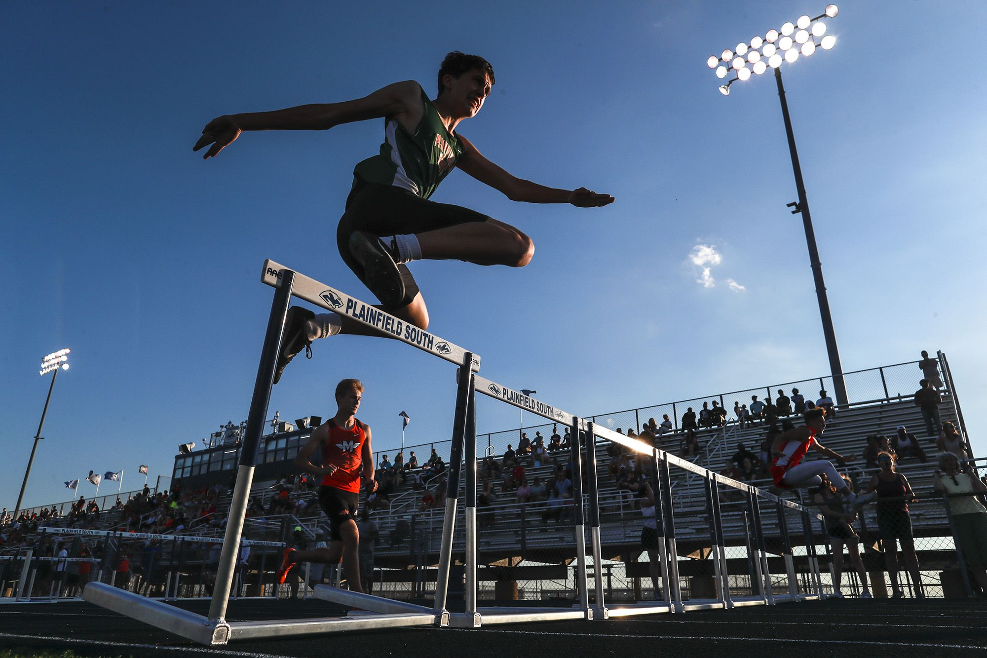 Plainfield East hurdler Dylen Callozzo clears the final hurdle on Saturday, June 5, 2021, at Plainfield South High School in Plainfield, Ill.