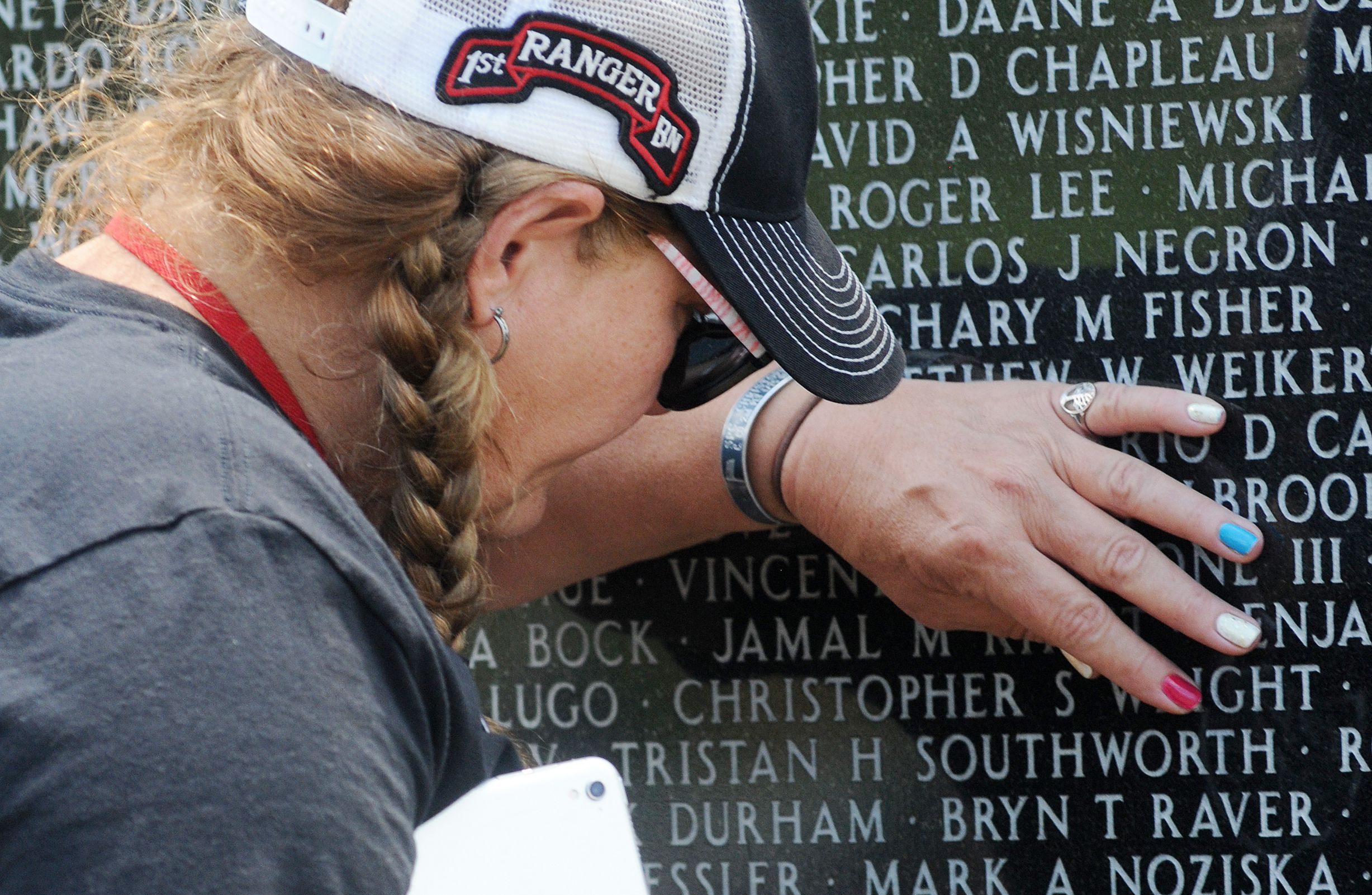 A Gold Star mom, Linda Wright-Dennis, of Jeffersonville, ind., runs her fingers over the engraving of her son's name, Army Spc. Christopher S. Wright, at the Middle East Conflicts Wall in Marseilles Saturday. He was killed in action on Aug. 19, 2010, and this was her first time seeing his name on the wall.