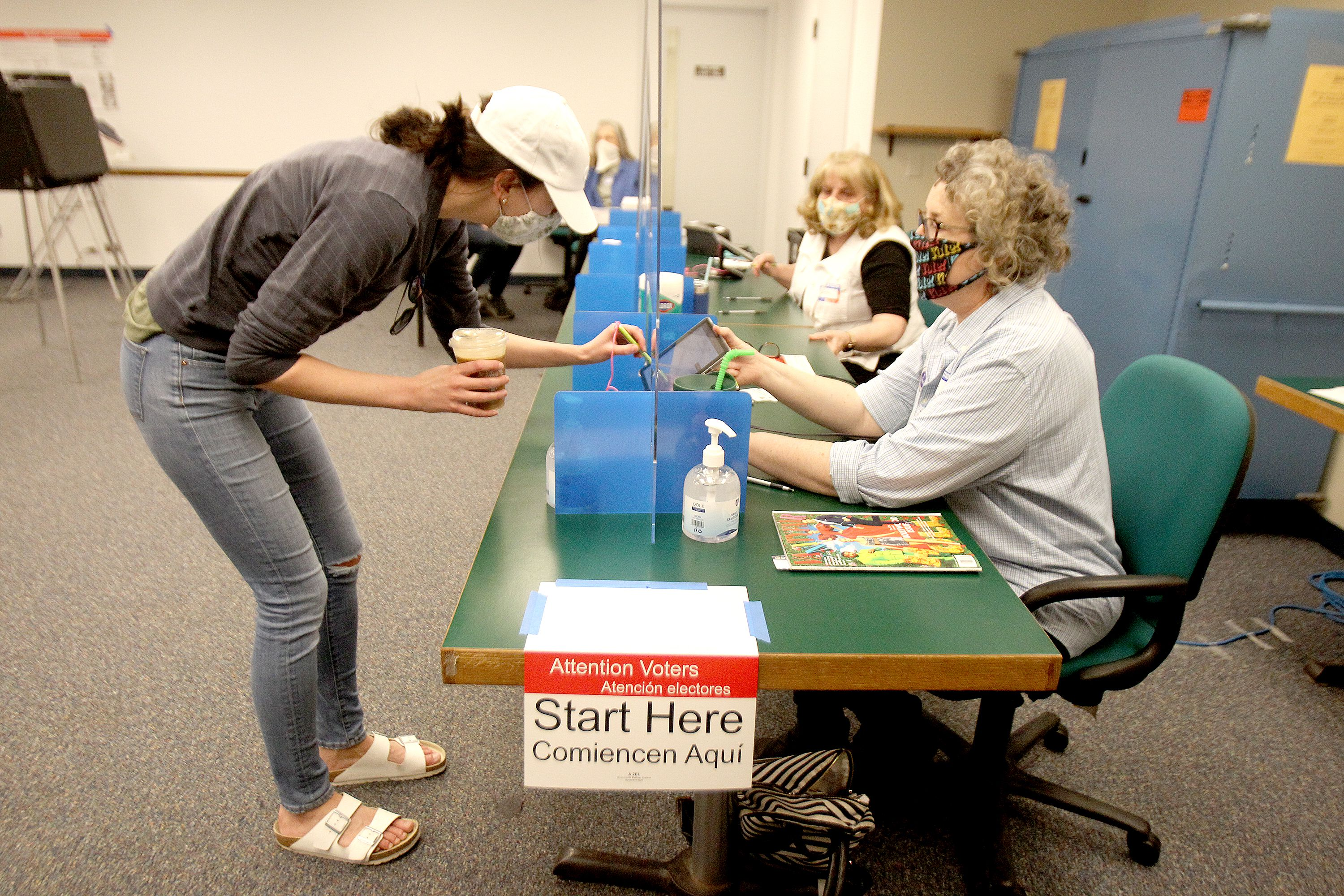 Kayla Petrey of Downers Grove is assisted by Election Judge Sheila McGlone during voting for the consolidated election at the Downers Grove Village Hall on Tuesday, April 6, 2021.