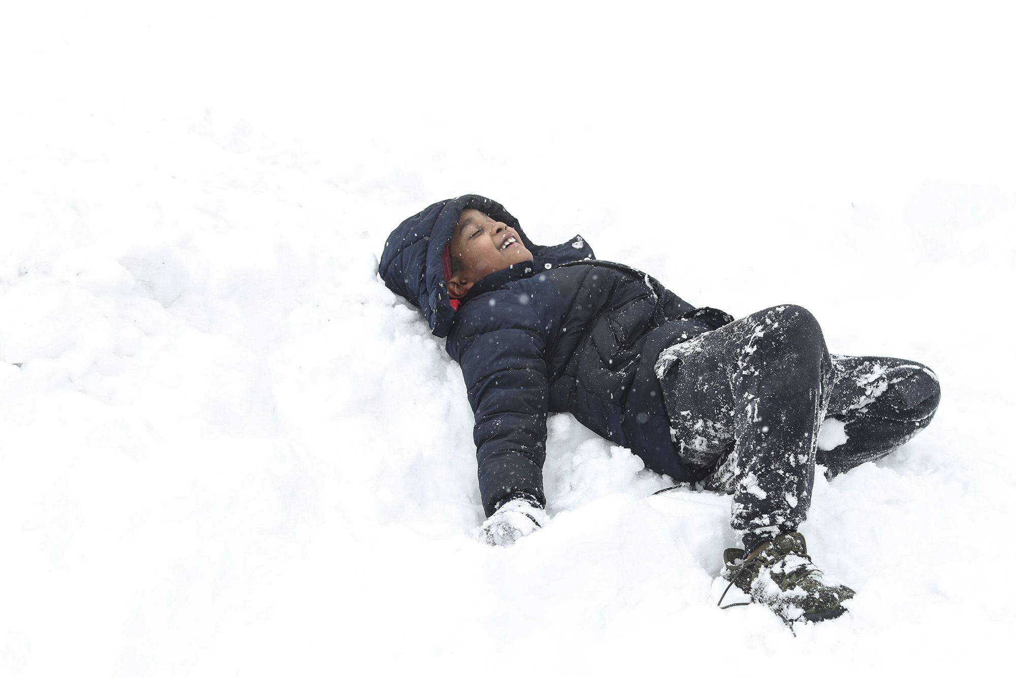 Derrick Stevenson III tries to make a snow angel on Sunday, Jan. 31, 2021, in front of his family's home in Joliet, Ill. Nearly a foot of snow covered Will County overnight, resulting in fun for some and challenges for others.
