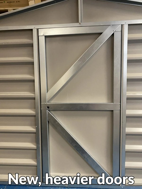 A heavy looking steel door with two 45 degree braced bars and a thick centre bar connecting them. Text at the bottom of the image reads 'new, heavier doors!'