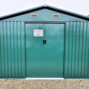 The 10ft x 10ft Shed in green on the grounds of the Sheds Direct iRELAND SHOWRROM IN NORTH DUBLIN. The base is a golden brown and the sky is bright blue. The shed is sturdy looking, the doors are closed and there is a pricelist stuck to the door.