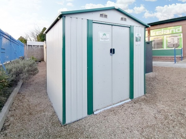 The 8ft x 6ft steel garden shed on the Sheds Direct Ireland lot. It's a white-white colour with green trim. It stands on cobblestones that are goldish in colour and the showroom walls are visible behind it.