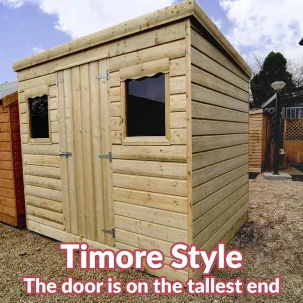 A timore style wooden cabin. It's seen from the right. The front and left side fo the shed are visible, the door is on the front and the roof slopes from the front to the back. There are two scalloped windows visible too
