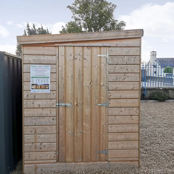 A cabin shed in the sheds direct Ireland showroom. It has a sloped room, a door which is not at ground level (there is a step up to it) and the wood pattern is horizontal. It is a pale wood and the steel hinges and lock are easily visible on it.