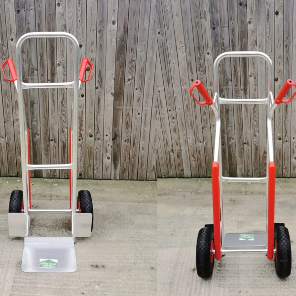 A front and back view of the Aluminium Sack Truck. The item is silver, except for the wheels which are black and the red handles and knee supports.
