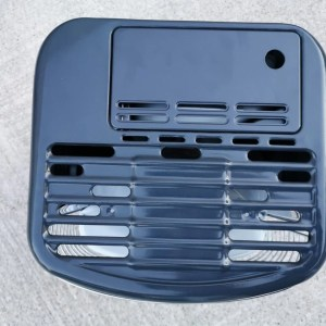 The top view of the Kero241a paraffin wick heater. It's square on three sides and it bulges into a semi-circle at the front. There is a grid on the circular side that you can almost see the burner through. The back end has a port where the fuel tank goes
