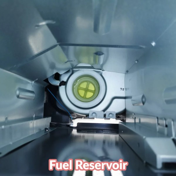 An internal view of the kero241a paraffin heater. It's shiny and metallic and there is a circular fuel reservoir at the bottom in which fuel is visible.