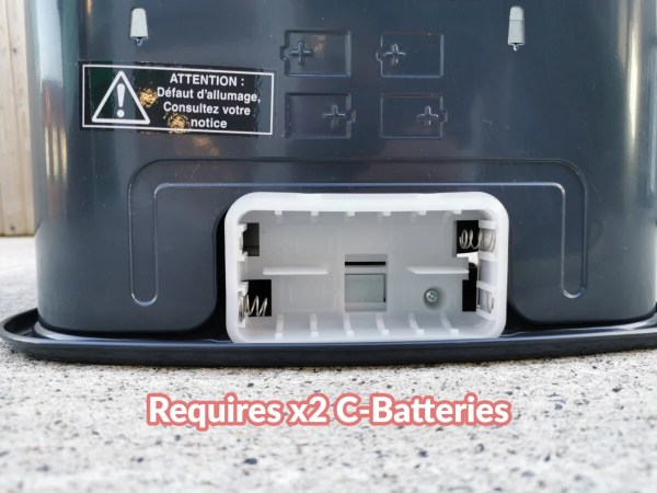 A close up view of the battery port on the back of the heater. Text overlaid states 'requires x2 C-Type batteries'
