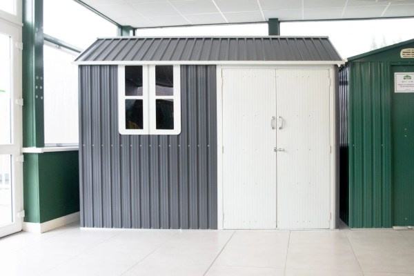 A steel Cottage shed on display in Baileborough, Cavan. It's grey with two double doors and a window. There are gutters to each side and firm grip handles on each door.