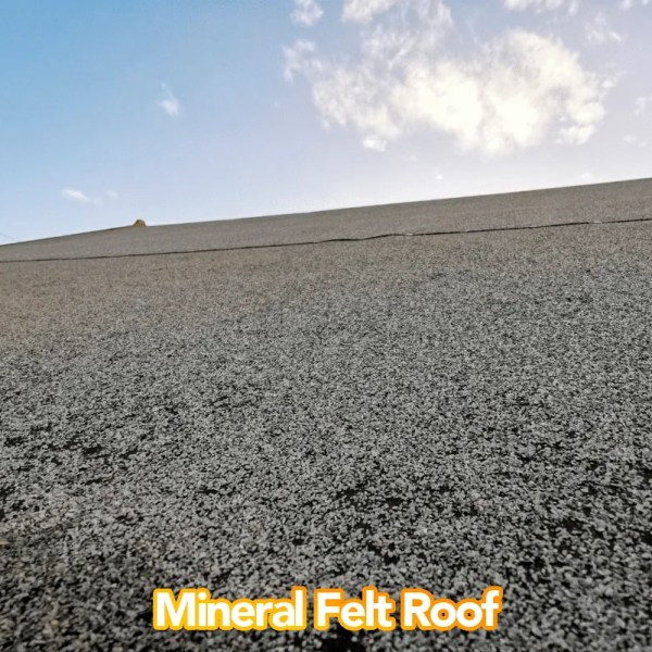 A close up on the mineral felt roof. It's black and tar-like, with a coarse surface. The photo is take from a low angle and the sky is visible above.