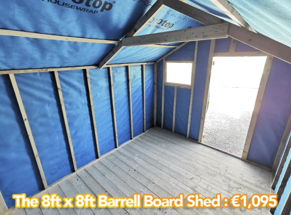 8x8 Barrell Board Shed as seen from inside. There is a blue lining on the walls and the door is open. The window is now to the left of the door.