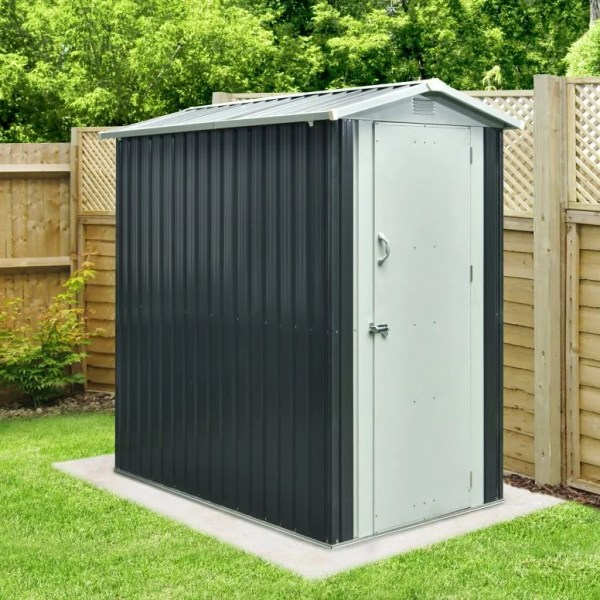The New 4x6 Steel Garden Shed from Sheds Direct Ireland. It's a dark grey in colour overall, with a lighter grey door and peaked roof. There is a handle on the door as well as a bolt-lock. There is a wooden wall behind the unit and to it's right hand side. It sits on a solid concrete base and there's a large tree behind it too!