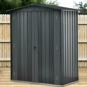 The Small Shed, free standing on decking in an Irish Garden. It is black in colour, with a slight grey sheen. There are two doors which are closed and a key in one of the doors. It is mini in size and quite beautifully finished
