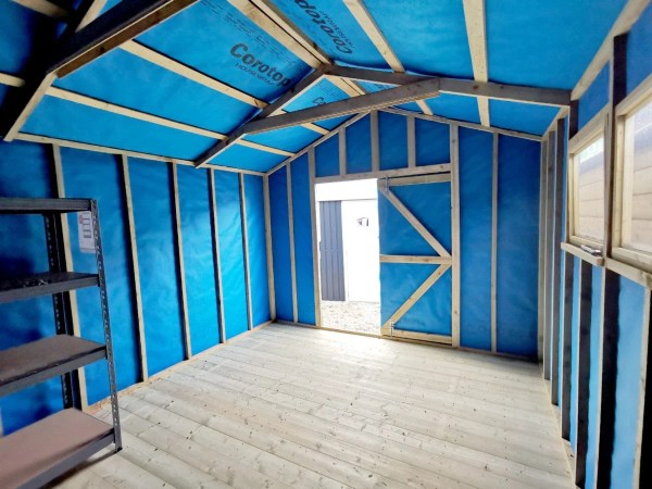 The internal view of a wooden shed, looking outwards. The light is pouring in the door and the walls have . abright blue membrane lining on them. There are thick wooden slats and two windows on the right hand side of the shed as we view it.