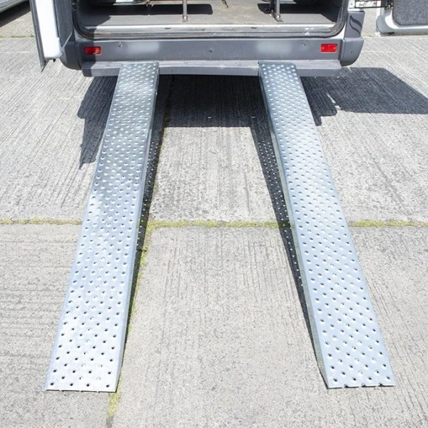 A view of the Steel Loading Ramps as seen from directly behind the bus that they are attached to. They are shiny and clean. There are extruded holes for grip. They support 1,500kg.