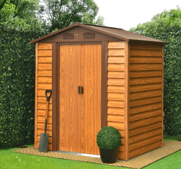 The 8ft x 6ft Wood Grain Steel Shed is sitting in a garden, close to a hedge. It is on a yellow-stone concrete base with hedges to two sides of it. There is a plant pot with a circular shrubbery in it and a shovel to the front of the shed