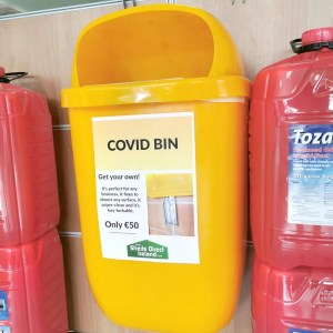 A single, shiny yellow bin mounted on a wooden surface. It's long and shaped like a medical tablet with a curved, smooth opening at the top which has a lipped hood. It has a sign on it which reads 'COVID Bin - perfect for any business reopening!'