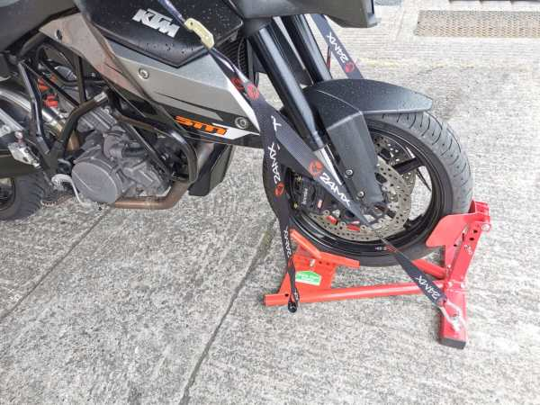 A side view of the bike in the sheds direct ireland motorbike stand. The straps are in use in the side ports, allowing the bike to freestand without assistance