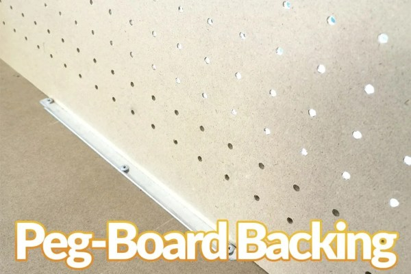 A close up of the joint between the peg-board and the middle shelf. The holes between the pegboard are letting light through.