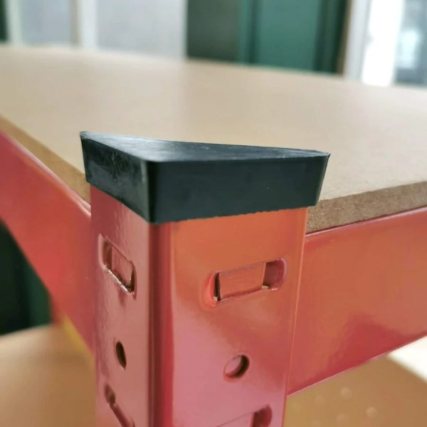 The edges of the work bench. It reads 'rubber capped edges!' on top of this in orange and white font. The rubber caps are smooth and black. They sit on the red metal edges of the bench.