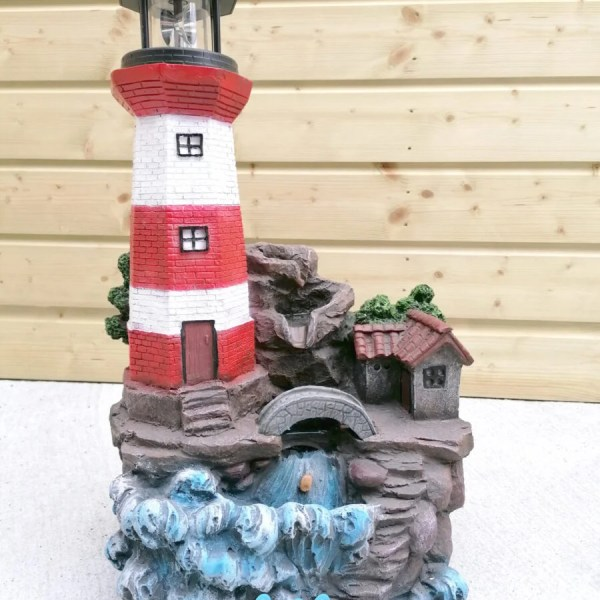 The Lighthouse Water Feature against a wooden shed