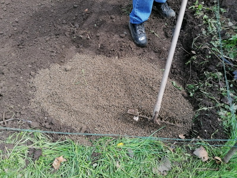 Laying a base for a steel shed: the gravel has been poured into the pit and it is being flattened by a rake