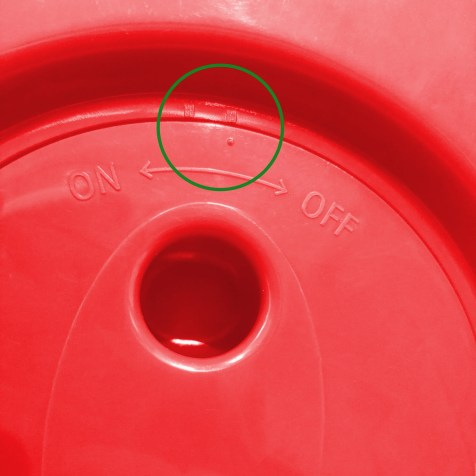 the bottom side of the pop up stool. there are two port holes which are used for turning the stool. Above these are two notches with 'on' written above one and 'off' written above the other. The stool is a vividly bright red.