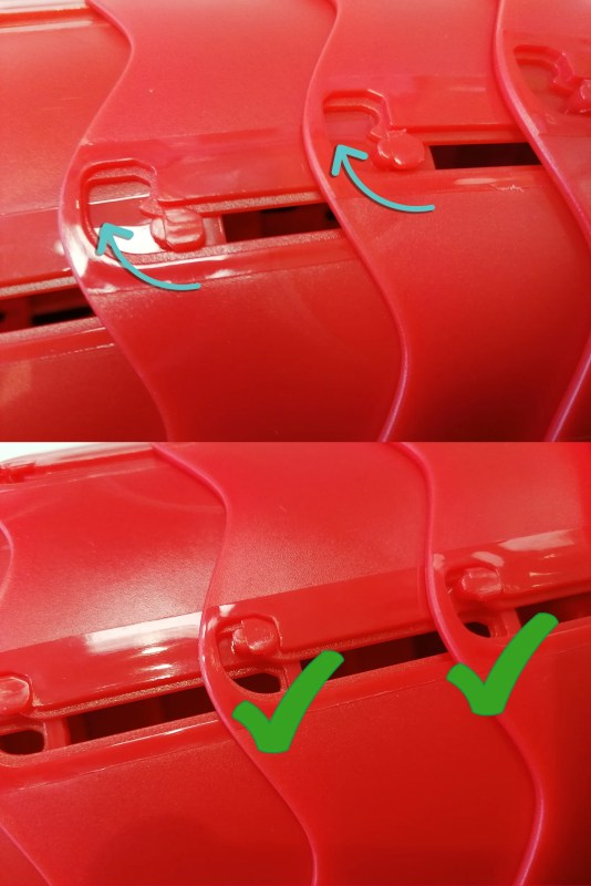 The red 'teeth' of the pop up stool being shown clicking into place, via a rotation of the handle upwards
