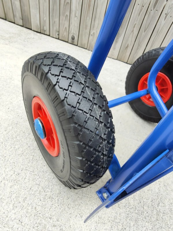 A close up view of the hard tyres on the blue hand truck. The tyres are a hard plastic and they have an internal red metal rim with a bright blue protective cap covering the centre