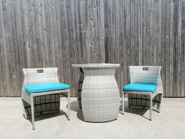 A picture of two balcony chairs on either side of a table. There is a brown fence behind the Balcony Furniture. There is a baby blue cushion on each of the chairs.