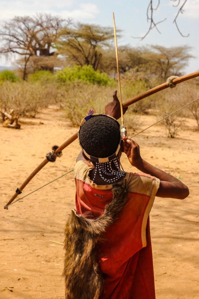 Ein Hadzabejunge übt Bogenschießen
