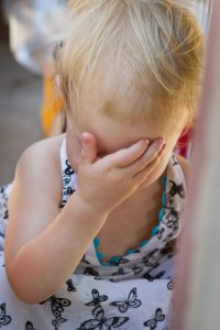 Image of toddler with hand over her face