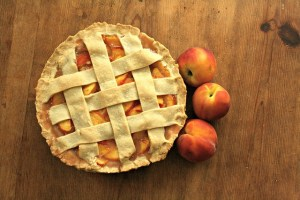 peach pie with peaches next to it