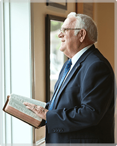 Jim Brackett looks out a window while holding his Bible
