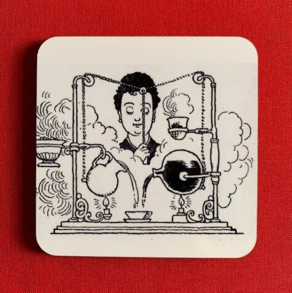 Photograph of a coaster, illustrated with the Super-De-Luxe Coffee Maker black and white line drawing and set against a red background.