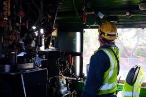 In this colour photograph taken on Ian Logan's camera a crew member checks equipment above the engineer's seat in the cab of Big Boy 4014.