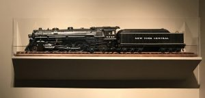 In this colour photograph a model of a Hudson type locomotive with the name New York Central on its tender is displayed in a glass case at the Albany Institute of History & Art.