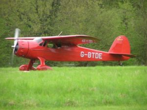 In this colour photograph Ian Logan lands one of his magnificent machines, a 1940 Cessna Airmaster, on a grass runway at Popham Airfield in Hampshire.