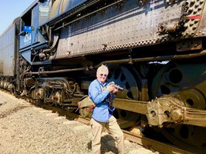 In this colour photograph Ian Logan stands with his camera beside Big Boy 4014, dwarfed by the driving wheels and gargantuan firebox.