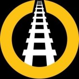 The We Are Railfans logo is a railway track printed white on black within an ochre circle.