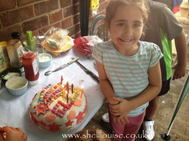 Ella at her birthday BBQ with her birthday cake