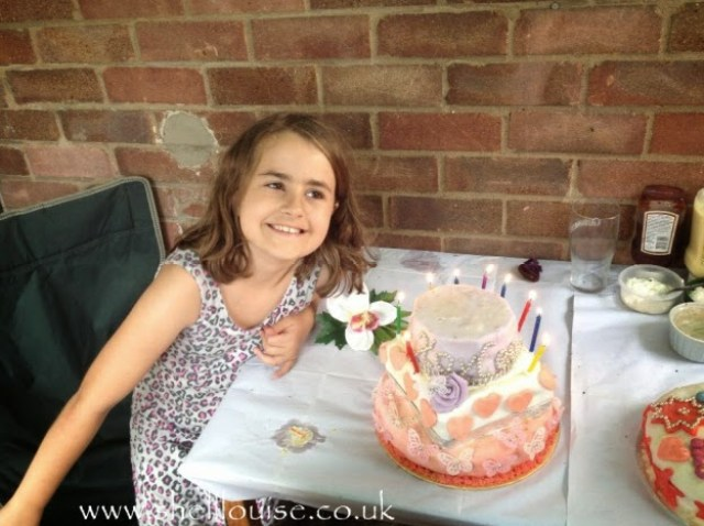 KayCee at her birthday BBQ, blowing out the candles on her cake