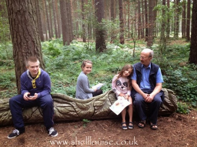 Ant, Aiden, KayCee and Ella sitting on a carved log