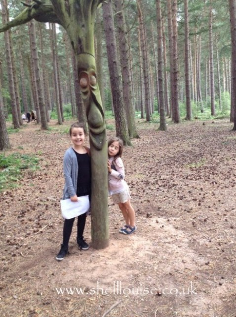 KayCee and Ella standing next to a tree with a face carved into it
