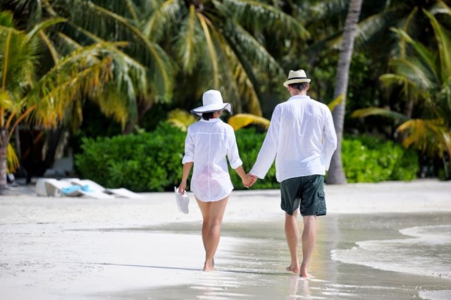 Couple walking hand in hand on a beach